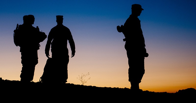 Image of silhouetted Soldiers in front of evening sky